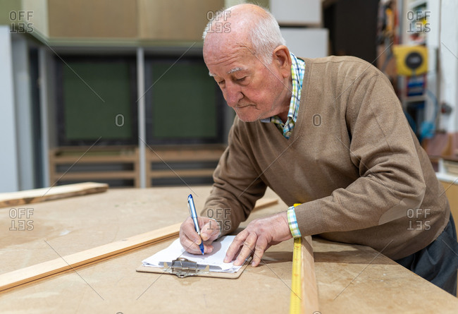 Concentrated elderly male artisan in casual clothes taking notes while working in joinery