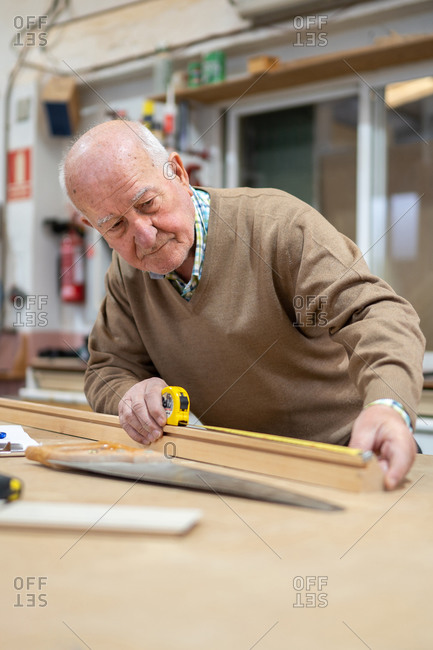 Elderly male woodworker measuring material with tape placed on machine in joiner