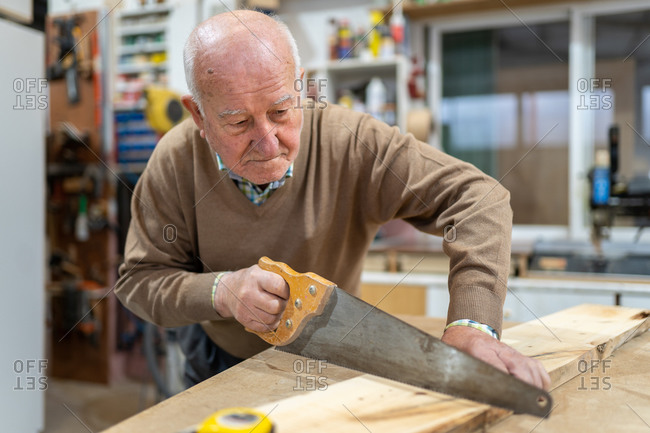 Focused senior male carpenter in casual clothes cutting wood with saw while working in professional joinery