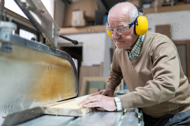 Focused adult elderly man artisan in goggles and headphones sawing wooden board with sharp circular saw in workshop