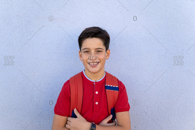 Adorable happy boy in red polo shirt standing near blue wall with backpack after school