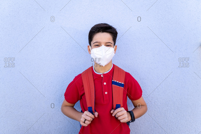 Adorable unrecognizable boy in red polo shirt and medical mask standing near white wall with backpack after school