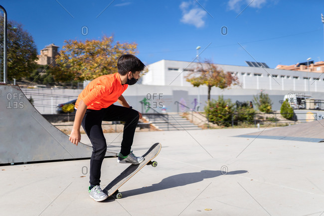 Full body of unrecognizable male teenager in casual clothes and face mask doing trick on skateboard during outdoor training against blue sky in park during coronavirus