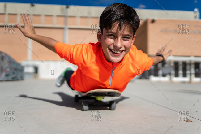 Cheerful ethnic teen boy in casual clothes lying on skateboard with outstretched arms and smiling during training on square on sunny day