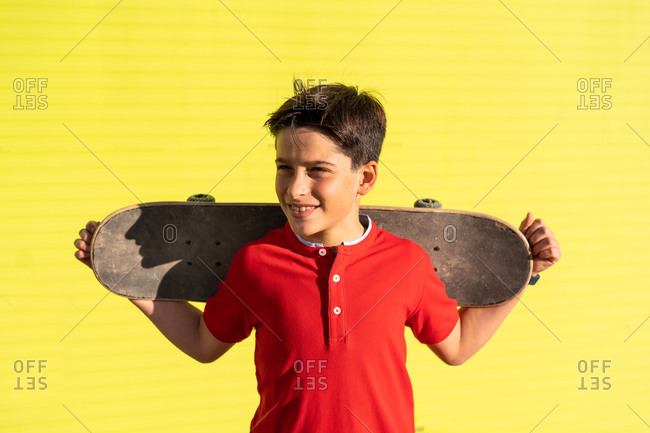 Happy teenage boy holding skateboard while standing in yellow background looking away
