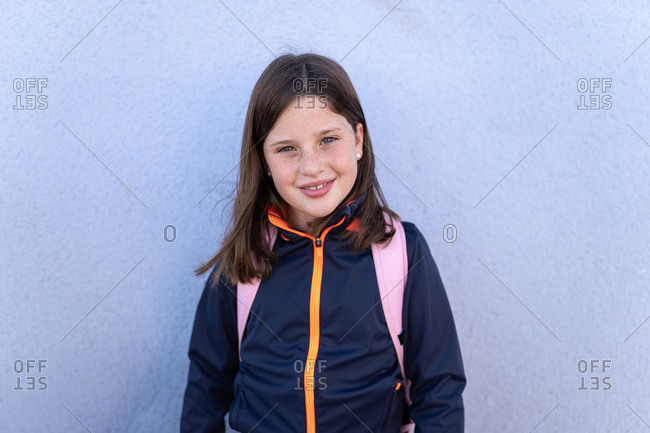 Cute happy little girl in casual clothes with backpack standing on street near white wall and looking at camera after school