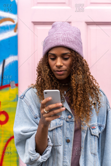 African American female teenager in trendy outfit and hat while reading message standing on street near pink door
