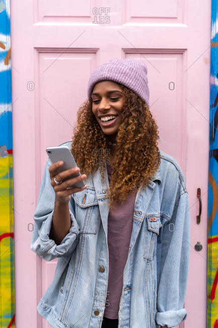 Cheerful African American female teenager in trendy outfit and hat smiling while reading message standing on street near pink door