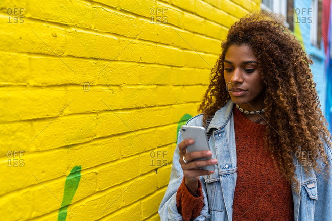 Content young African American female millennial with long curly hair in casual outfit browsing on smartphone while walking on cobblestone street near colorful building with abstract graffiti