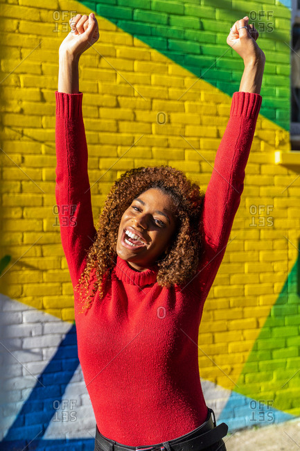 Excited young ethnic lady with long curly hair in casual clothes screaming with fists up while standing on street near colorful graffiti wall
