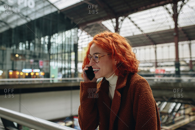 Delighted female with red hair and in autumn coat standing at railroad station and speaking on mobile phone while enjoying conversation