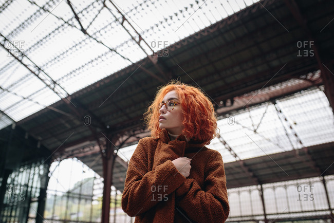 Low angle of stylish female with red hair and in warm coat standing at railway station and looking away