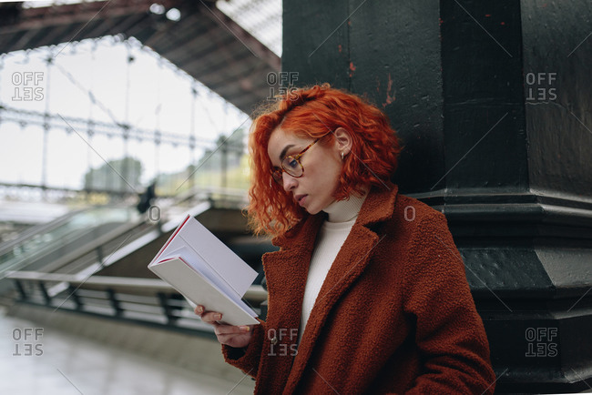 Tranquil female with red hair standing at railroad station and reading interesting book