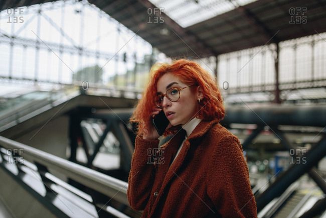Serious female with red hair and in autumn coat standing at railroad station and speaking on mobile phone while enjoying conversation
