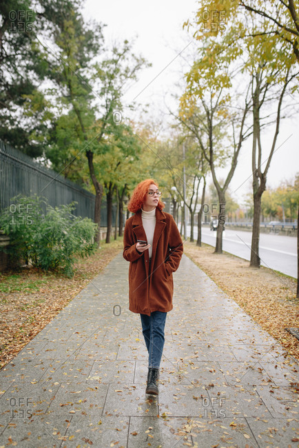 Optimistic female with red hair and in autumn coat standing on alley in park and enjoying smartphone conversation with friend