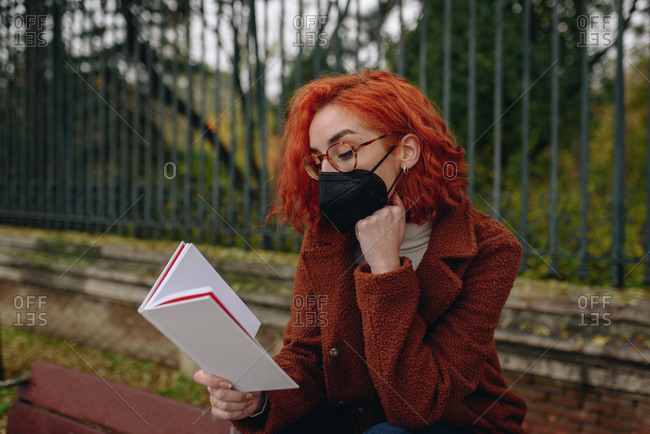 Thoughtful female with red hair and in protective mask sitting on bench in park and reading interesting book while relaxing in city during coronavirus epidemic