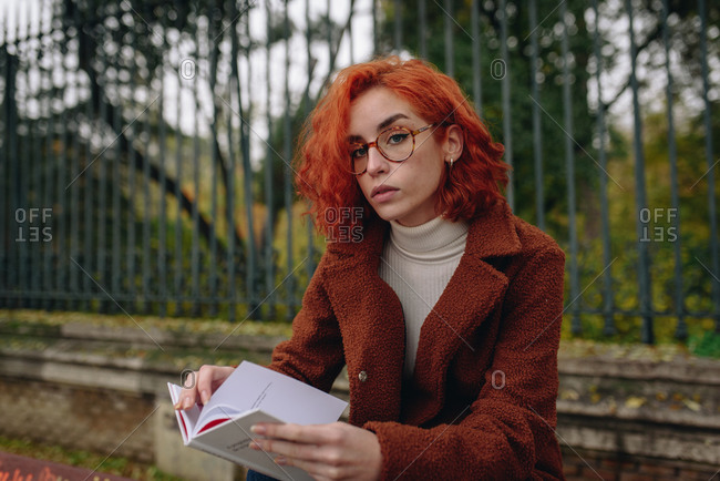 Thoughtful female with red hair sitting on bench in park and reading interesting book while relaxing in city during coronavirus epidemic