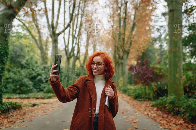 Optimistic female with red hair and in autumn coat standing on alley in park and taking selfie