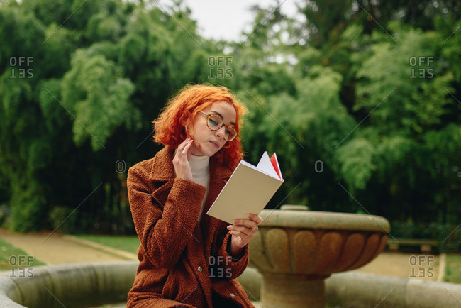 Focused female with red hair sitting in park and reading interesting story in book while enjoying weekend alone