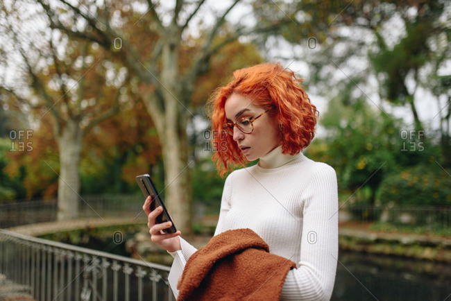 Tranquil female with red hair standing in park and surfing Internet on smartphone while enjoying weekend