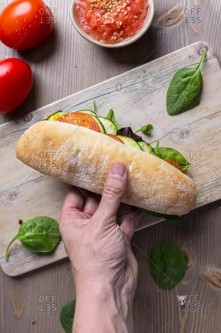 Hand holding a panini of zucchini and tomatoes