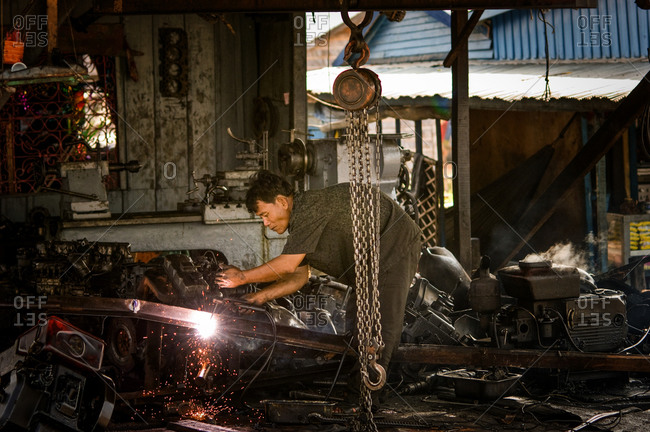 Mechanic, Phnom Penh, Cambodia - 28 March 2008: Cambodian Man Welds In Workshop For Petrol Engines.