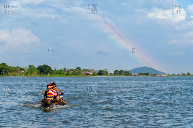 Floating Village, Kompong Chnang, Cambodia - 15 November 2008: Small Fishing Boar Crosses River Returning To Floating Village With Rainbow In Back Ground.