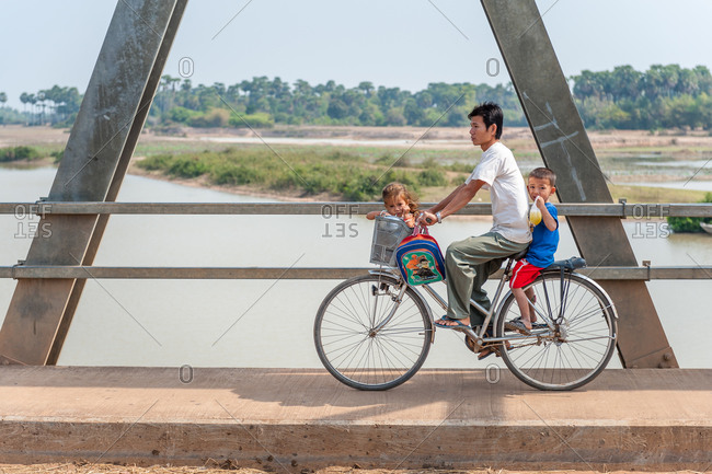 Family On Bike Crossing Bridge, Kompong Thom Cambodia - 03 February 2009: Small Child Sits On Basket Of Fathers Bicycle.