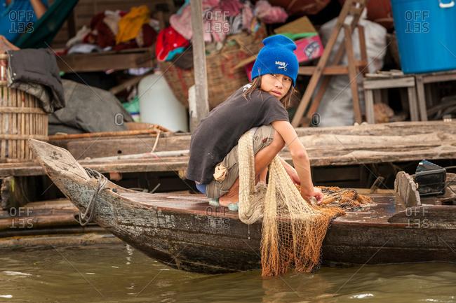 Floating Village, Kompong Chnang, Cambodia - 06 September 2009: Young Khmer Fisherman Removes Debris From His Fishing Net.