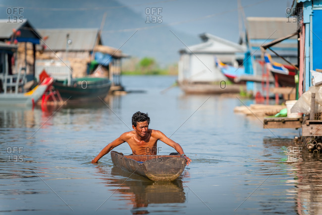 Floating Village, Kompong Chnang, Cambodia - 06 December 2009: Elder Khmer Man Paddles By Hand Through Floating Village In Dug Out Canoe In  Warm Evening Light.