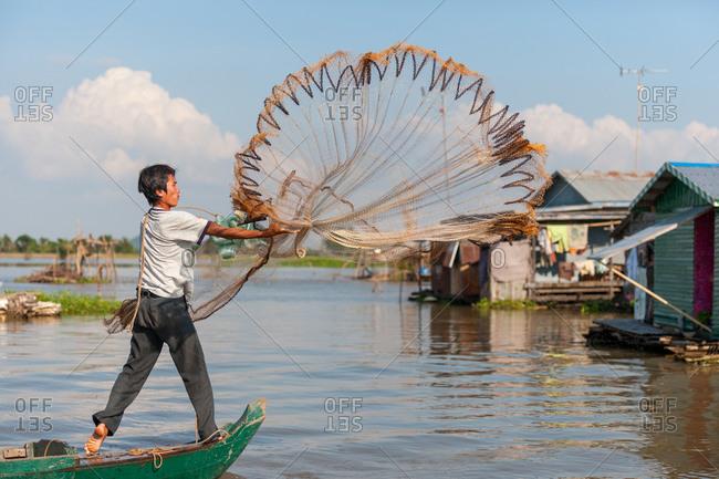 Floating Village, Kompong Chnang, Cambodia - 13 December 2009: Fisherman Throws Fishing Net From Traditional Wooden Fishing Boat Makes Nice Pattern.