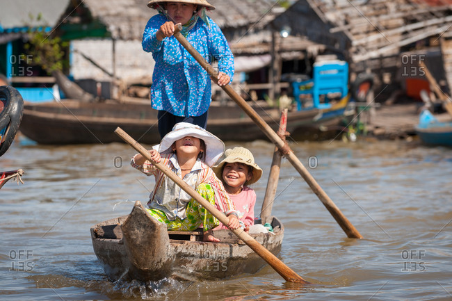 Floating Village, Kompong Chnang, Cambodia - 17 January 2010: Young Khmer Girls Help Mother Row Boat As Hat  Falls Over Her Eyes In Warm Evening Light.