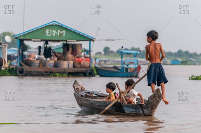 Floating Village, Kompong Chnang, Cambodia - 29 April 2010: Young Khmer Boy Transports His Younger Brothers Across River Home After School.