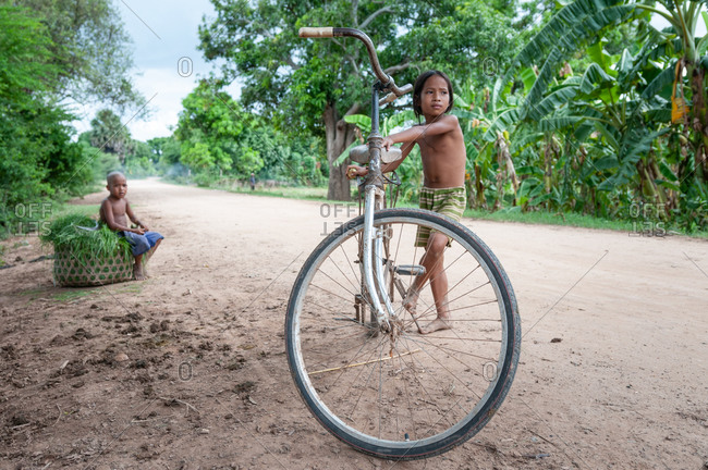 Silk Island (Koh Dach), Cambodia - 19 June 2010: Young Khmer Children With Bicycle Waiting For Parents To Come Back To Take Heavy Basket Of Animal Feed Grass.