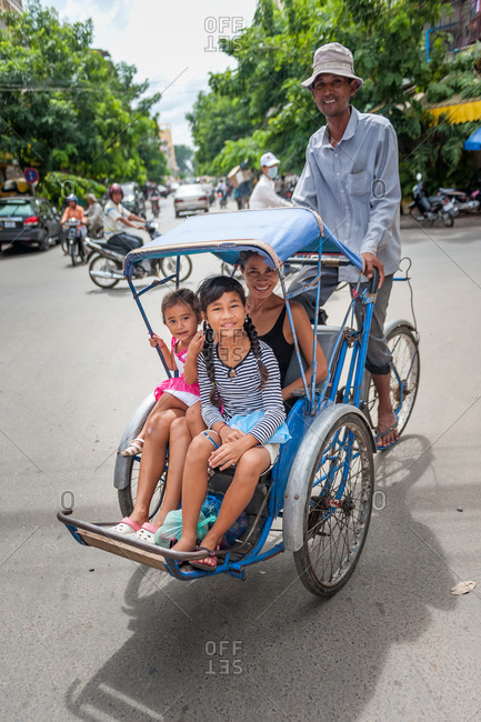 Classic Cyclo, Phnom Penh, Cambodia - 24 July 2010: Typical Cycle Rickshaw With Passengers In Street Area.