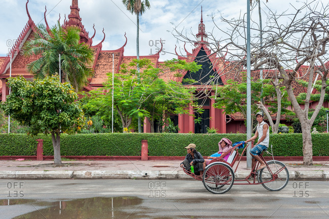 Cyclo Driver, National Museum,  Phnom Penh, Cambodia - 24 July 2010: Cycle Rickshaw Casually Passes On Off Phnom Penh'S Most Iconic Buildings.