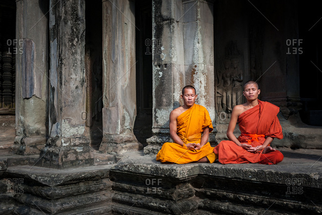 Monks In Angkor Wat, Angkor Park, Siem Reap, Cambodia  - 04 November 2010: 2 Monks Meditate In Inner Courtyard On Upper Tier Of Main Temple.