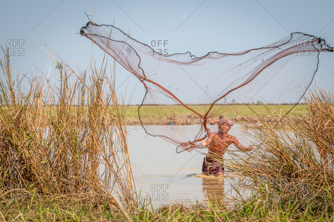Throwing Fishing Net, Siem Reap Province, Cambodia - 21 January 2011: Local Khmer Fisherman Uses Traditional Fishing Method To Catch Fish.
