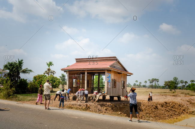 Moving House, Cambodia - 04 February 2011: Local Khmer Men Move House On Wheels Down The Road By Hand To New Plot Of Land.