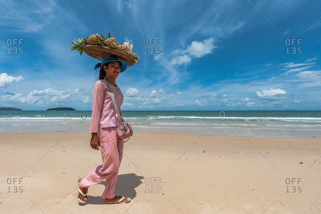 Sihanoukville, Cambodia - 24 May 2011. Freelance Khmer Sells Woman Walks The Beach Selling Fresh Pineapples.