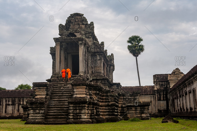 Monks In Angkor Wat, Angkor Park, Siem Reap, Cambodia  - 30 May 2011: 2 Monks Climb Up Steps To Old Library In Main Temple Whilst Tourist Photographs Them.