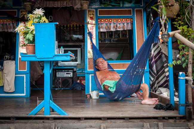 Floating Village, Kompong Chnang, Cambodia - 17 July 2011: Old Man Sleeps In Hammock Of Simple Floating House.