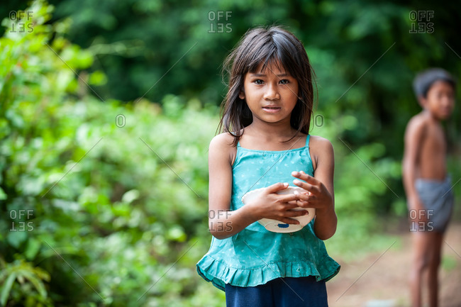 Portrait, Kompong Chnang, Cambodia - 10 August 2011: Young Khmer Girl Finishing A Snack Outside Her House With Her Brother.