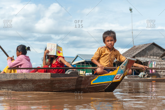Floating Village, Kompong Chnang, Cambodia - 10 August 2011: Young Khmer Boy Rows Through Floating Village In Warm Evening Light.
