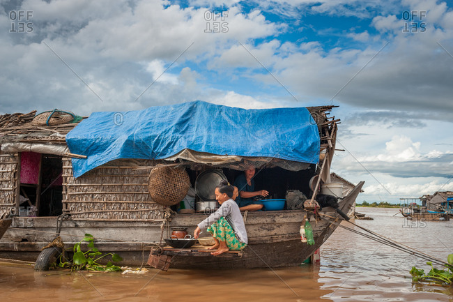 Floating Village, Kompong Chnang, Cambodia - 10 August 2011: Khmer House Wife Washes Dishes In River From House Boat.