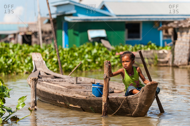 Floating Village, Kompong Chnang, Cambodia - 21 August 2011: Young Khmer Girl Takes A Rest From Rowing Through Floating Village In Warm Evening Light.
