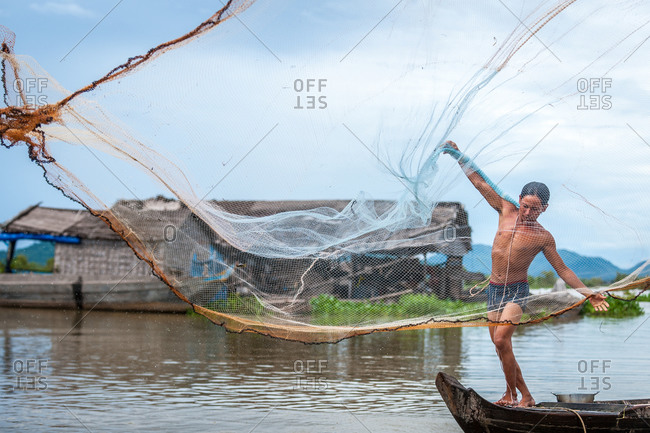 Floating Village, Kompong Chnang, Cambodia - 28 August 2011: Fisherman Throws Fishing Net From Traditional Wooden Fishing Boat.