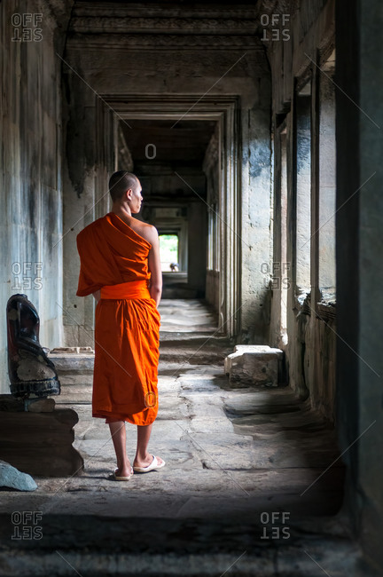 Monk In Angkor Wat, Angkor Park, Siem Reap, Cambodia - 08 October 2011: Lone Monk Walks Through Upper Gallery Of Main Temple While Looking Out Of Window.