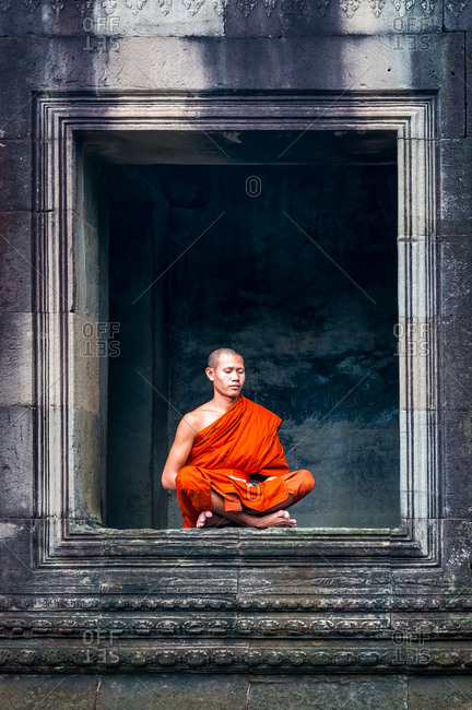 Monk In Angkor Wat, Angkor Park, Siem Reap, Cambodia - 08 October 2011: Lone Monk Meditates In Window Of Upper Gallery In Main Temple.