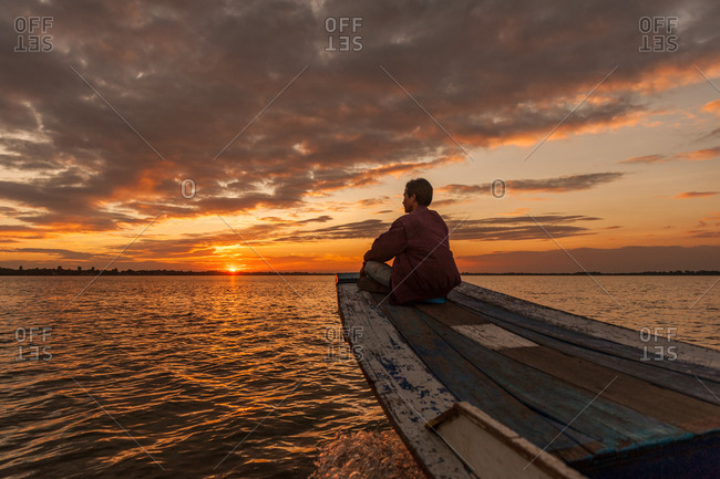 West Baray, Angkor Park, Siem Reap Province, Cambodia - 31 December 2011: Cambodian Man Enjoys Sunset As Boat Crosses Water.